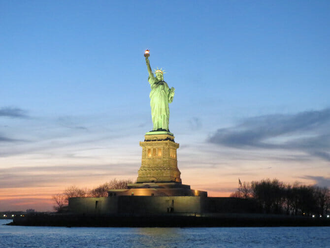 Statue of Liberty by sunset during a boat tour New York